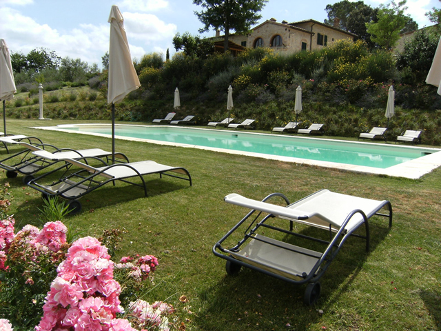 Swimming Pool of the romantic Farmhouse Taverna di Bibbiano Tuscany Siena San Gimignano, surrounded by roses and flowers of any kind and a splendid view of the countryside